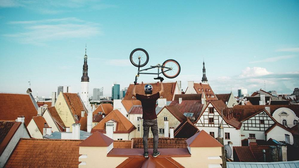 Biker standing on a red roof in the Old Town of Tallinn, in Estonia